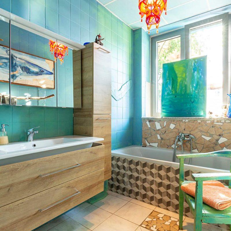 Kleines Badezimmer mit Badewanne und Duschmöglichkeit. Toilette und Pissoir befinden sich in einem separaten Raum direkt gegenüber.