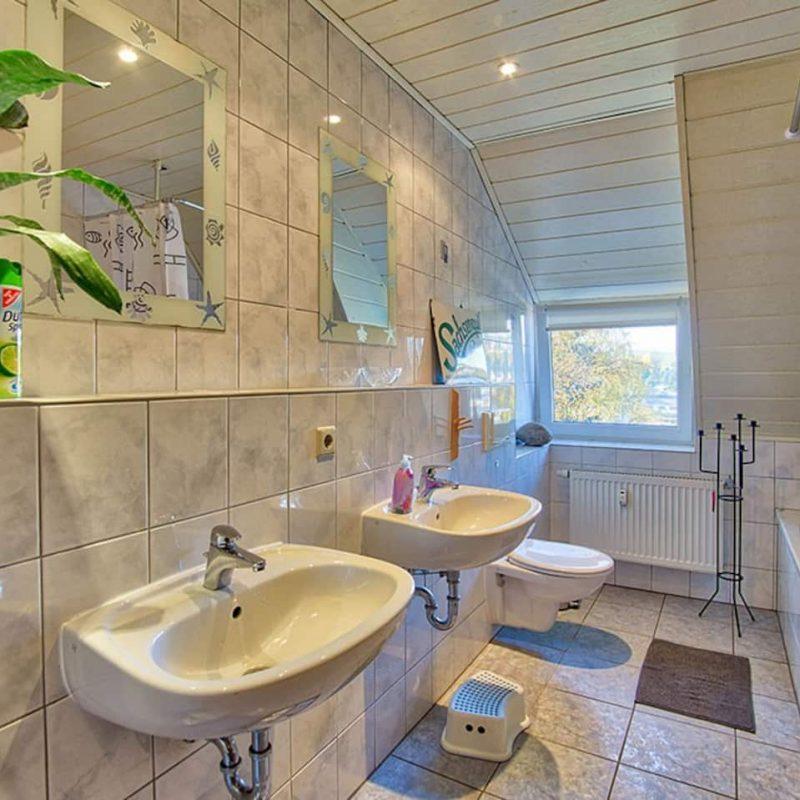 Helles Bad mit Doppelwaschbecken und Badewanne.