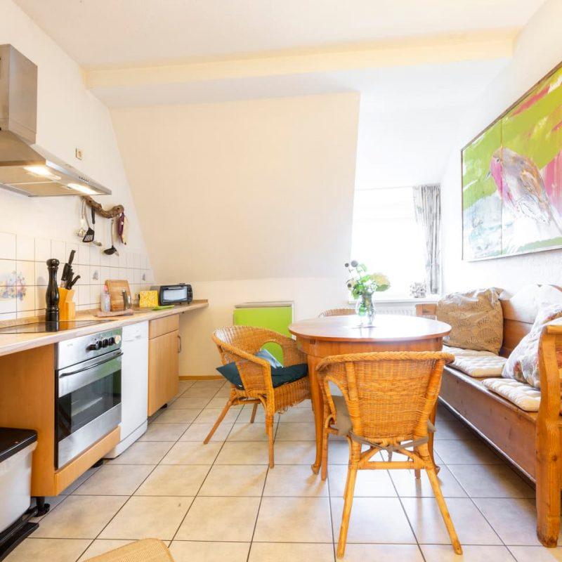 Küchenbereich mit ausziehbarem Esstisch und gemütlicher Küchenbank.