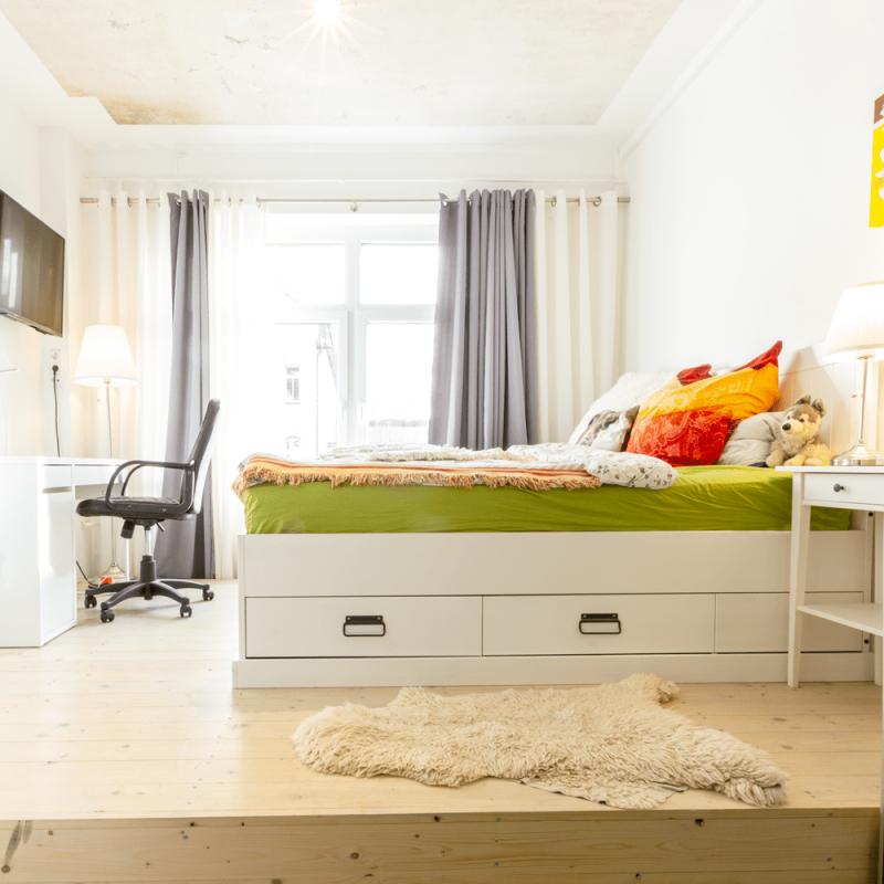 Vogel trifft Hase – frisch renovierter, stilvoll eingerichteter Raum mit Podest, TV und Gäste-WC.