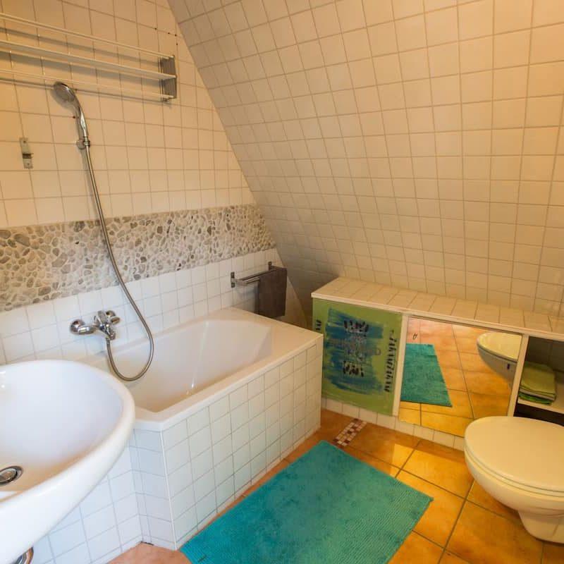 Badezimmer mit Toilette und Spiegel.