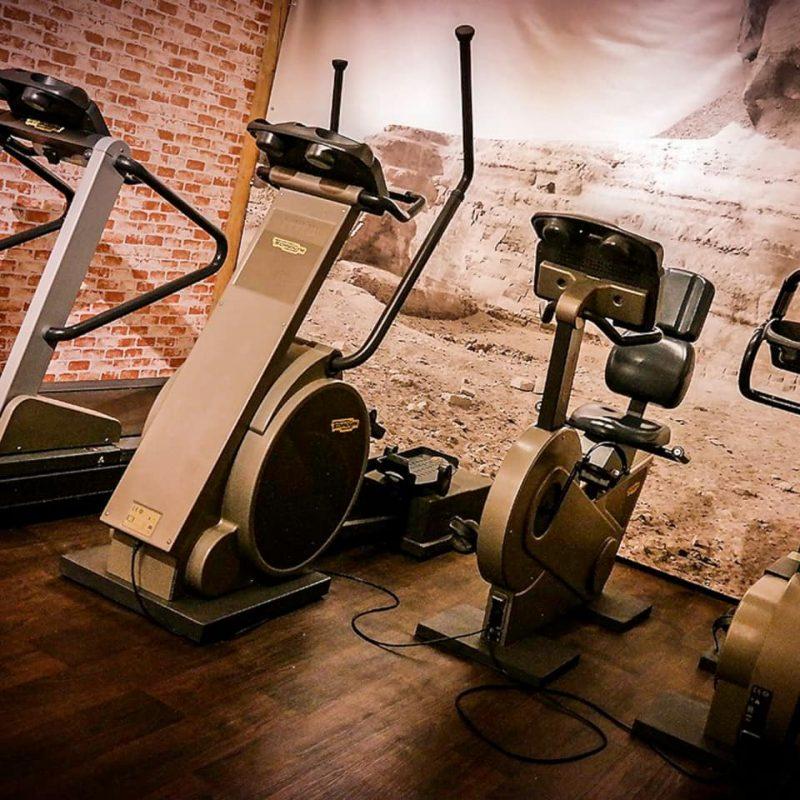 Fitnessraum mit vier verschiedenen Sportgeräten.