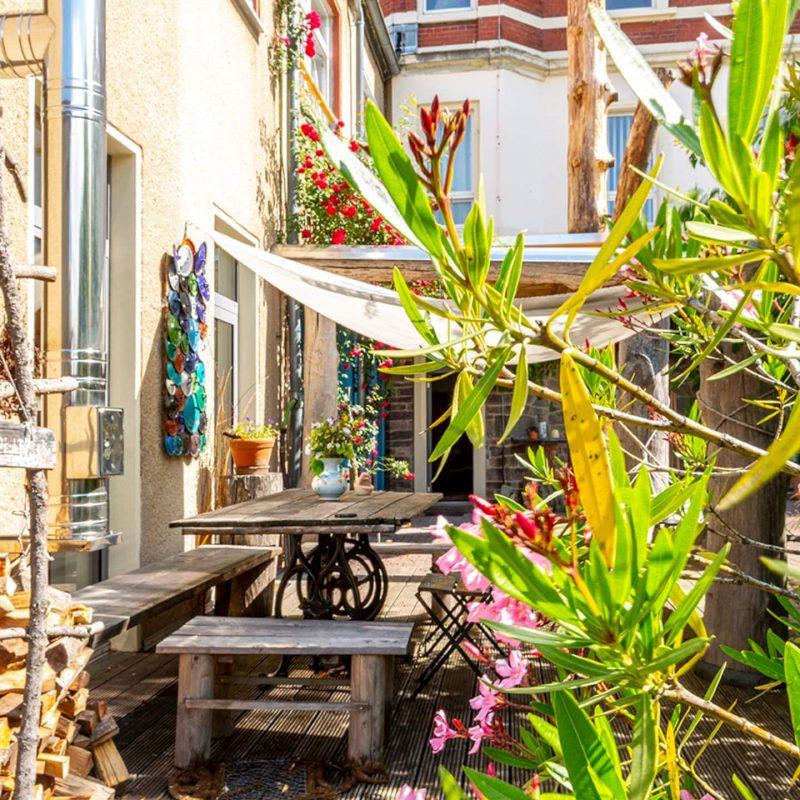 Frühstücksoase auf der Gemeinschaftsterrasse – hier zwitschern Simpel, Meise und Nachtigall mitten in der Bergstadt.