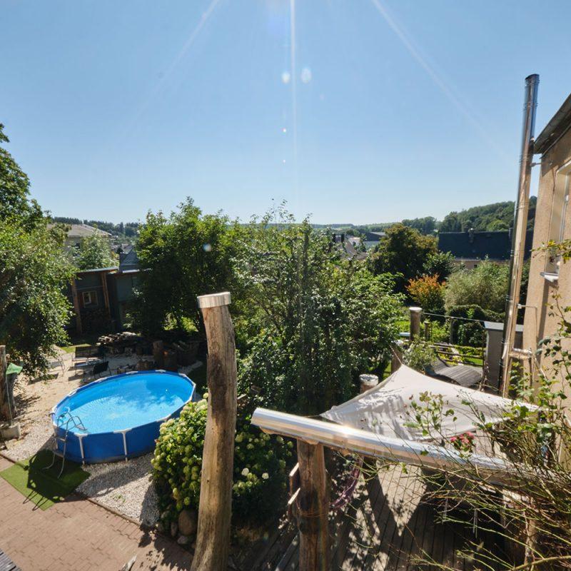 Balkon mit Ausblick auf großzügigen Garten.
