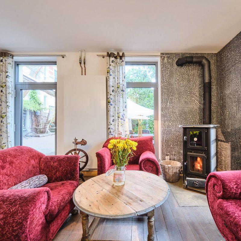 Gemütliche Sitzecke mit Kaminofen – ausgestattet mit Backrohr für leckrere Aufläufe oder einfach warme Semmeln zum Frühstück.